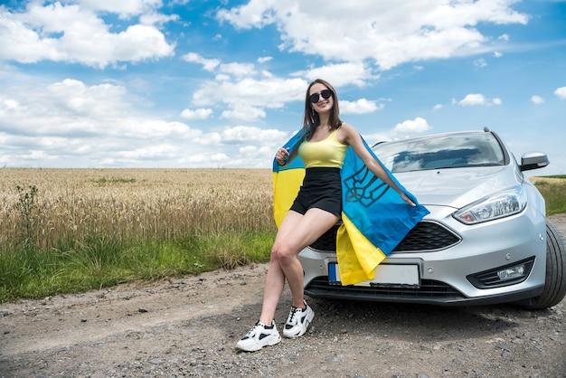 Felice bella giovane donna con bandiera dell'ucraina in piedi vicino alla sua auto in estate road
