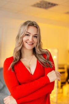Felice bella giovane donna con un sorriso in un elegante abito rosso con scollatura al chiuso, festa del fine settimana