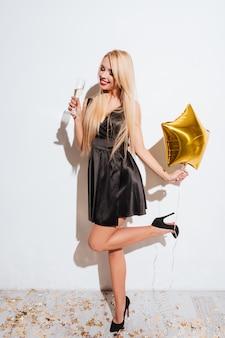 Felice bella giovane donna con palloncino a forma di stella in piedi e bere champagne su sfondo bianco