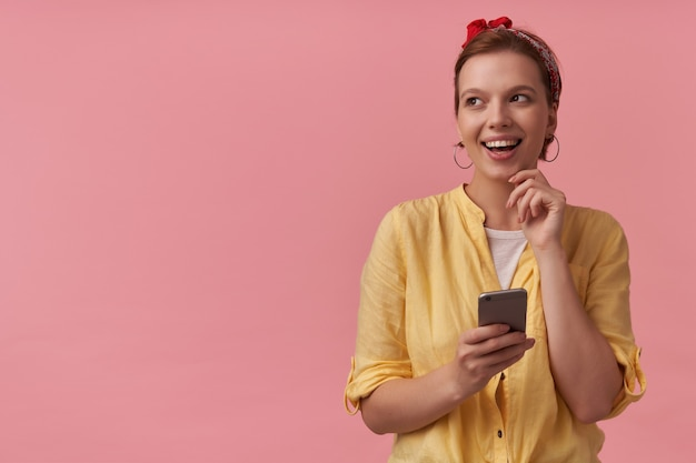 Felice bella giovane donna in camicia gialla con fascia sulla testa utilizzando il telefono cellulare e guardando lontano al lato sopra il muro rosa