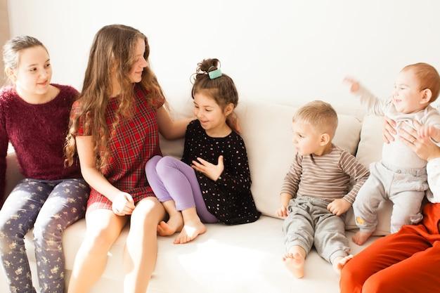 Felice grande famiglia di fratelli e sorelle seduti sul divano nella stanza bianca