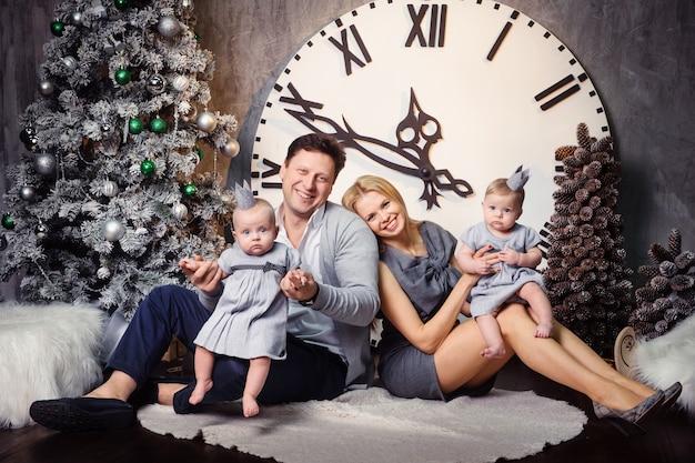 Una grande famiglia felice con bambini gemelli all'interno della casa di capodanno sullo sfondo di un grande orologio.