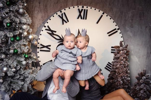 Una grande famiglia felice con bambini gemelli nell'interno della casa di capodanno sullo sfondo di un grande orologio