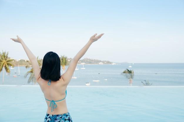 Bikini felice donna sulla piscina e mare nuvole cielo.