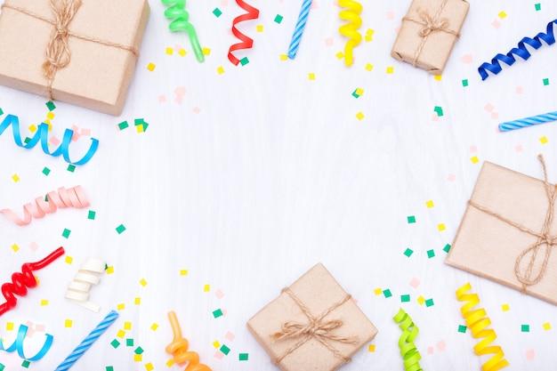 Sfondo di buon compleanno con regali colorati, coriandoli, candele, stelle filanti.