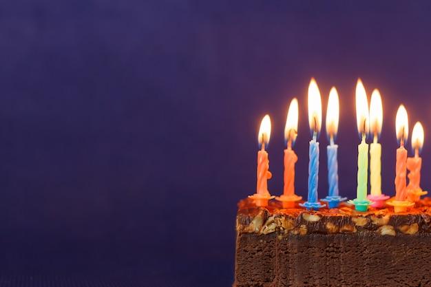 Torta di brownie di buon compleanno con arachidi, caramello salato e candele accese colorate su sfondo viola. copia spazio per testo.