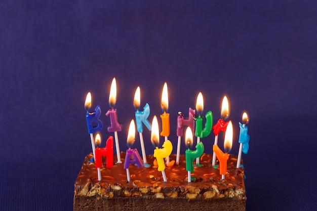 Torta di brownie di buon compleanno con arachidi, caramello salato e candele accese colorate sulla superficie viola. copia spazio per testo.