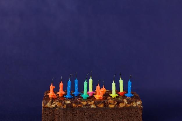 Torta di brownie di buon compleanno con arachidi, caramello salato e candele colorate non illuminate sullo sfondo viola. copia spazio per testo.