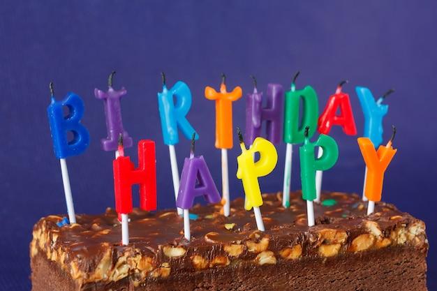 Torta di brownie di buon compleanno con arachidi, caramello salato e candele colorate non illuminate sulla viola. copia spazio per testo.