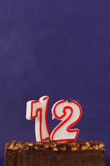 Torta di brownie di buon compleanno con arachidi, caramello salato e candele colorate non illuminate sulla superficie viola. copia spazio per testo. numero 72