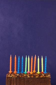 Torta di brownie di buon compleanno con arachidi, caramello salato e candele colorate non illuminate sulla superficie viola. copia spazio per testo.