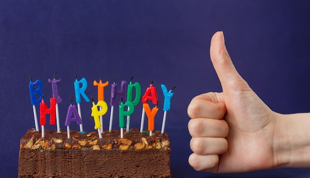 Torta di brownie di buon compleanno con arachidi, caramello salato e candele colorate non illuminate sulla superficie viola. la mano mostra come.