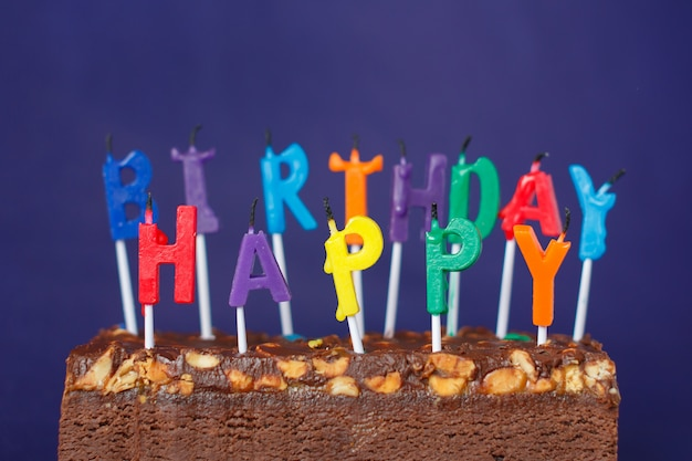 Torta di brownie di buon compleanno con arachidi, caramello salato e candele colorate non illuminate sulla parete viola. copia spazio per testo.