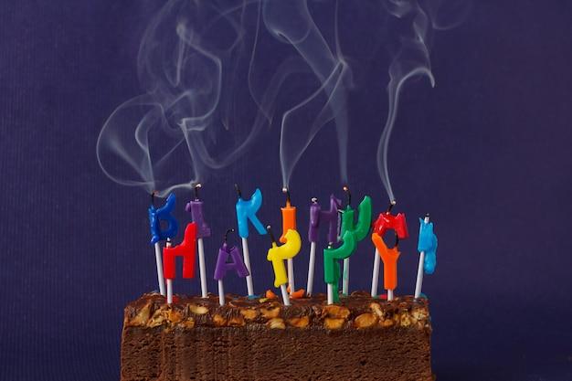 Torta di brownie di buon compleanno con arachidi, caramello salato e candele di fumo colorate non illuminate sulla parete viola copia spazio per testo.