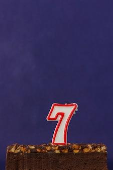 Torta di brownie di buon compleanno con arachidi, caramello salato e candele non illuminate sulla superficie viola. copia spazio per testo. numero sette 7