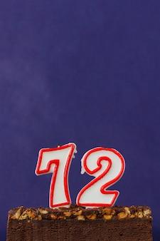Torta di brownie di buon compleanno con arachidi, caramello salato e candele non illuminate sulla parete viola. copia spazio per testo. numero 72