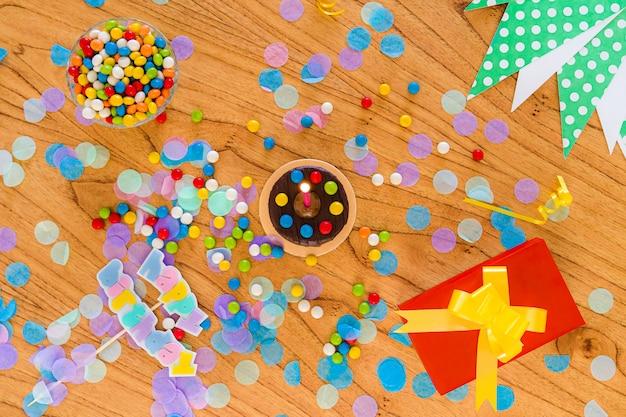 Buon compleanno concetto. torta, confezione regalo, cioccolatini, coriandoli e articoli per feste sparsi sul tavolo. vista dall'alto