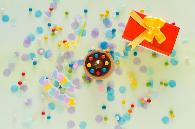 Buon compleanno concetto. torta, confezione regalo, coriandoli e articoli per feste sparsi sul tavolo. vista dall'alto