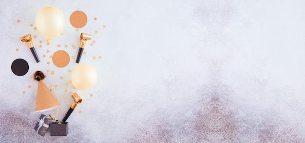 Buon compleanno e sfondo regalo con decorazioni in oro, palloncini e coriandoli. contesto festivo panoramico