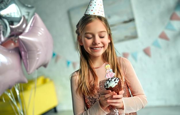 Buon compleanno! ragazza che spegne le candeline sulla torta di compleanno. festa della principessa. la stanza è decorata con palloncini.