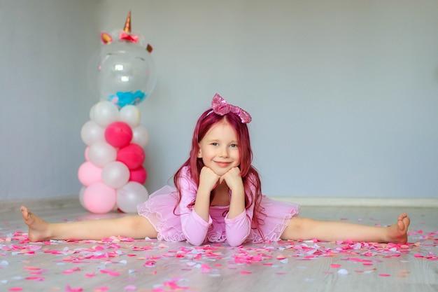 Ragazza di buon compleanno con coriandoli sul pavimento seduto su uno spago