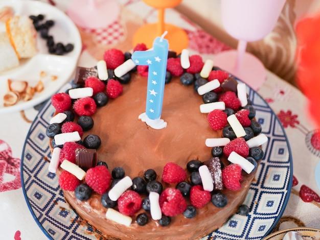Buon compleanno torta natalizia con candele saluti di compleanno biglietto d'auguri celebrare la festa di compleanno con splendida barretta di cioccolato. prima torta di compleanno con il numero 1, uno in cima. concetto del primo anno.