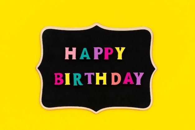 Iscrizione di buon compleanno da lettere colorate su tavola di legno.