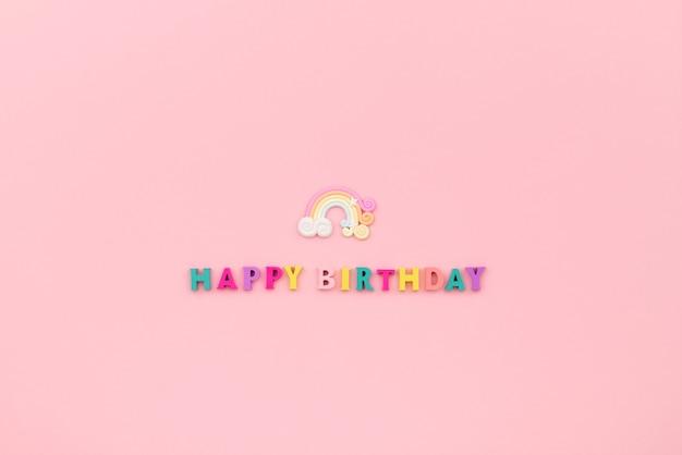 Iscrizione di buon compleanno da lettere colorate in legno con arcobaleno.