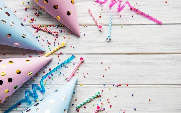 Buon compleanno o sfondo di una festa. lay piatto con cappelli di compleanno, coriandoli e nastri su fondo di legno bianco. vista dall'alto. copia spazio.