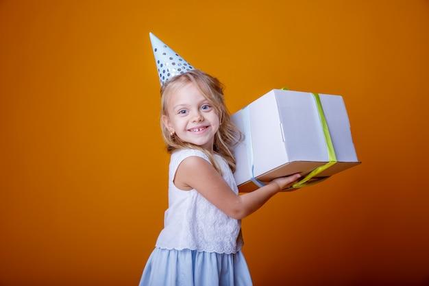 Buon compleanno ritratto di una ragazza bambino su uno sfondo giallo colorato con un regalo in mano