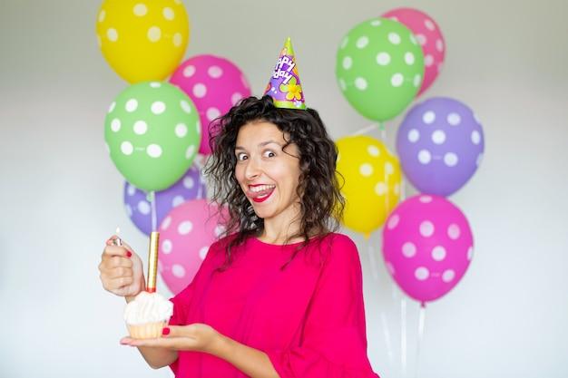 Buon compleanno. ragazza brunetta sexy in posa con palloncini, fuochi d'artificio, palloncini colorati e torta di festa su sfondo bianco.