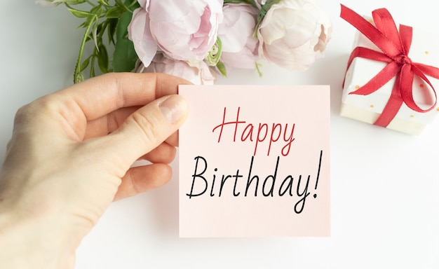 Testo di buon compleanno sulla carta in mano davanti a fiori rosa e confezione regalo