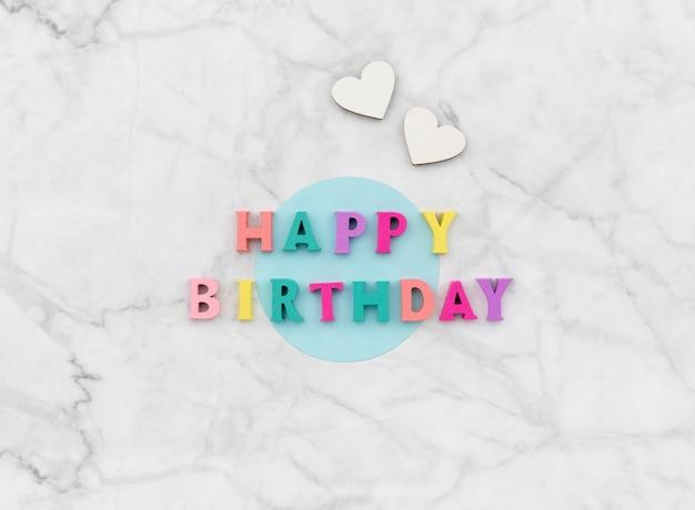 Testo di buon compleanno da lettere colorate in legno con cuori.