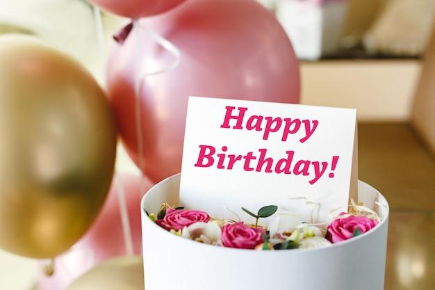 Testo di buon compleanno sulla carta regalo in fioriera vicino festivo palloncini rosa e oro. bellissimo bouquet di rose fiori freschi in scatola con biglietto di auguri di buon compleanno.