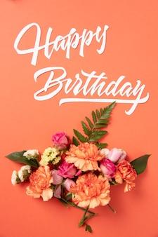Buon compleanno con composizione di fiori
