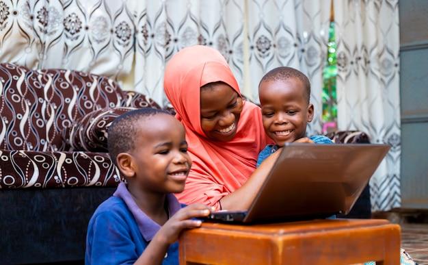 Felice madre single musulmana africana nera con due bambini che utilizzano la tecnologia modem