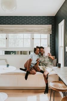 Felice coppia nera che si fa un selfie con una tavoletta digitale