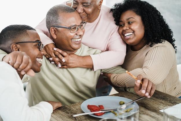Famiglia nera felice che mangia pranzo a casa - padre, figlia, figlio e madre che si divertono insieme seduti a tavola - focus principale sul viso dell'uomo