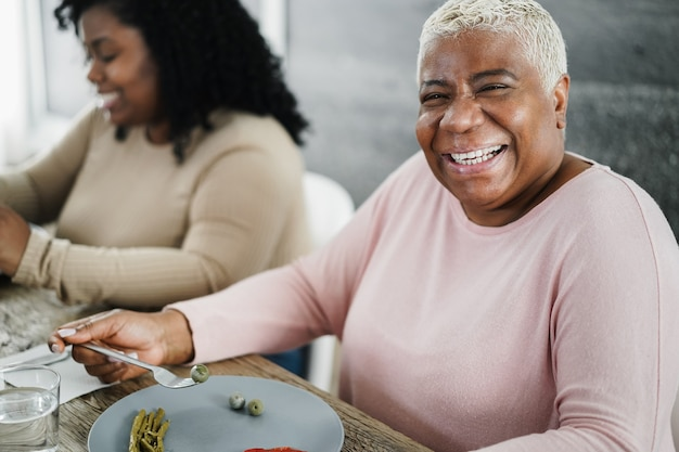 Famiglia nera felice che mangia pranzo a casa. madre e figlia, divertirsi insieme seduti a tavola