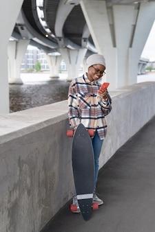 La ragazza nera felice con il longboard ha letto il messaggio nell'applicazione di chat dello smartphone all'aperto sorridente