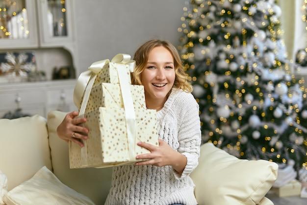 Happy black lady che tiene e abbraccia scatole regalo