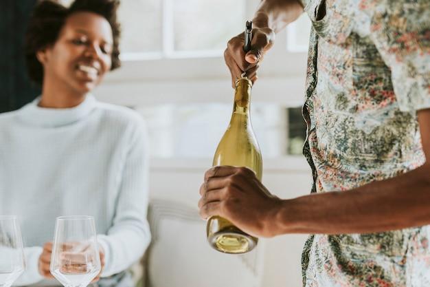 Uomo di colore felice che stappa una bottiglia di vino