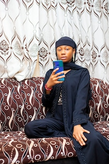 Felice ragazza adolescente musulmana nera con app per smartphone che si gode una videochiamata di chat virtuale online con gli amici in una riunione virtuale di chat mobile a distanza, registrando storie per i social media a casa.