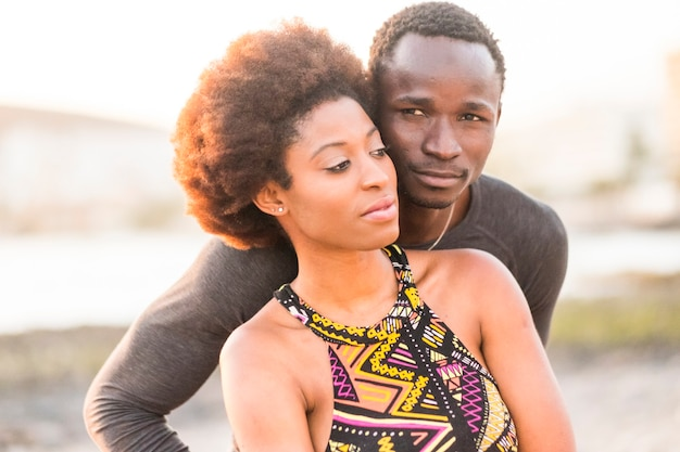 Felice razza nera coppia africana in spiaggia innamorata e godendo l'attività del tempo libero insieme seduti vicino alla costa dell'oceano estate e ama le vibrazioni per i giovani in vacanza