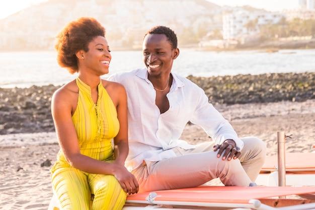 Felice razza nera coppia africana in spiaggia sorridendo e godendo l'attività di svago insieme seduti vicino alla costa dell'oceano estate e ama le vibrazioni per i giovani in vacanza