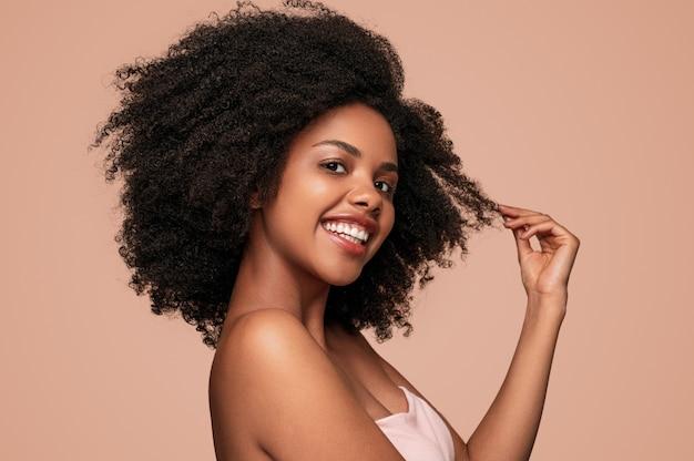 Donna nera felice che tocca i capelli puliti