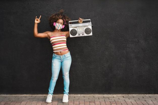 Felice donna nera che indossa la maschera protettiva per il viso divertendosi e ballando mentre si tiene una radio retrò - focus sul viso