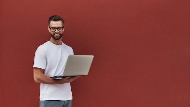 Felice blogger bel giovane in abiti casual e occhiali con laptop e guardando