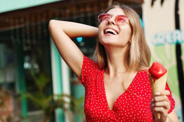 Felice ragazza bionda godendo l'estate, mangiando il gelato per le strade, sorridendo e guardando il cielo