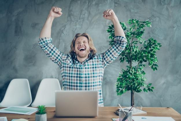Ragazzo biondo felice in posa in ufficio alla scrivania